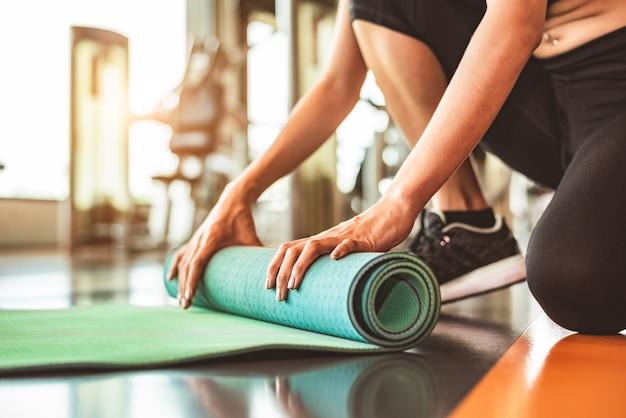スポーツフィットネスジムトレーニングセンターのバックグラウンドでヨガのマットレスを折るスポーティな女性のクローズアップ。