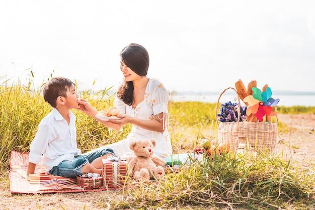 ピクニックをするとき美しいアジアのお母さんは草原で彼女の息子におやつを食べます。