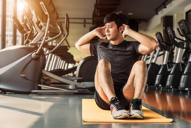 スポーツマンのクランチやマンションのフィットネスジムでヨガマットの上の姿勢に座る