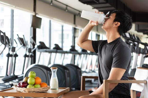 タンパク質を飲むハンサムな男は、毎日体を栄養補給するために牛乳とさまざまな種類の果物を振る
