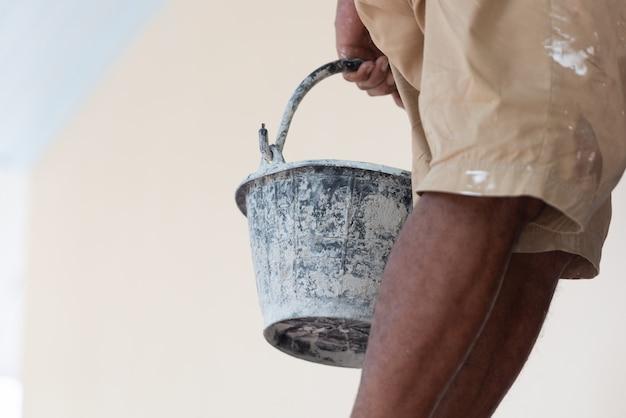 黒いペンキのバケツと画家の足のクローズアップ。建築および土木工学の概念