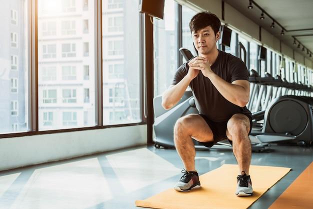 都市のマンションでフィットネスジムでヨガマットにスクワット姿勢をしているスポーツ男
