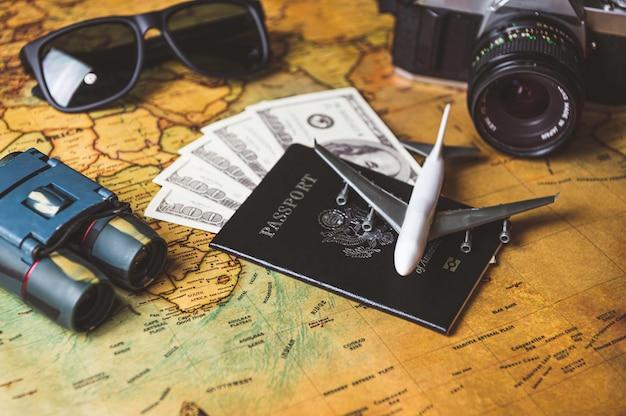 アメリカのパスポートと飛行機で観光客が小道具と旅行用アクセサリーを計画