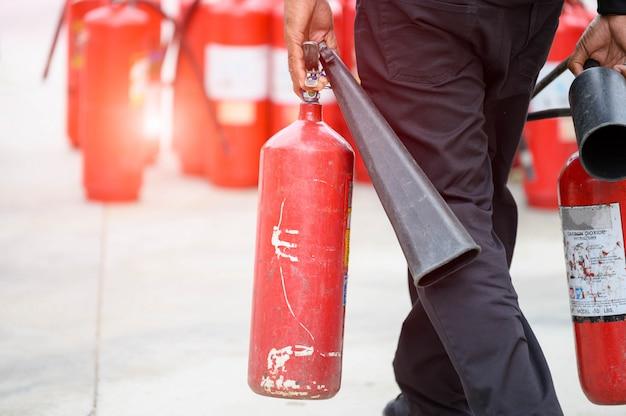 消防士の下半身のクローズアップは、携帯用消火器を保持することにより、火災訓練を準備します