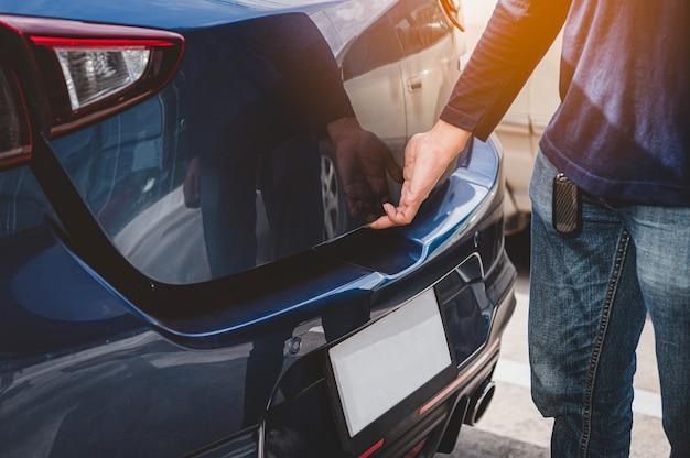 Крупным планом мужской руки открытия багажника хэтчбек, касаясь двери датчика