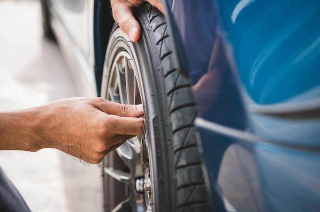 クローズアップ男性自動車技術者がタイヤの空気注入のためのタイヤバルブの窒素キャップを削除します。