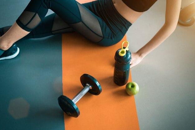 ジムの床に健康的な運動器具を持つフィットネス女性