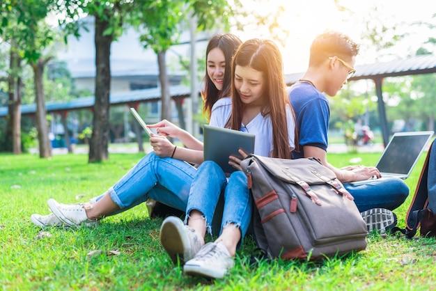 Группа азиатских студентов колледжа, используя планшет и ноутбук на поле травы на открытом воздухе