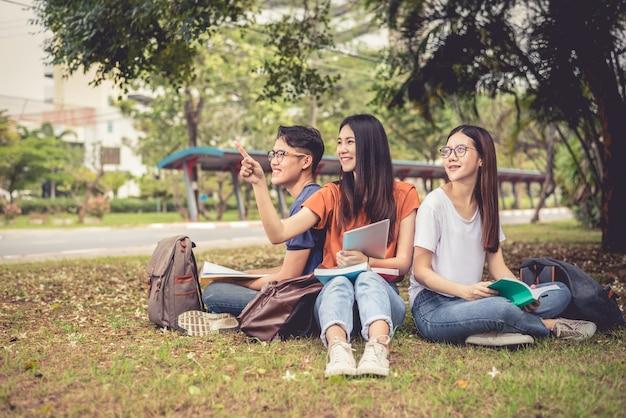 Группа азиатских студентов колледжа, читающих книги и репетитор английского языка специальность для экзамена на поле травы