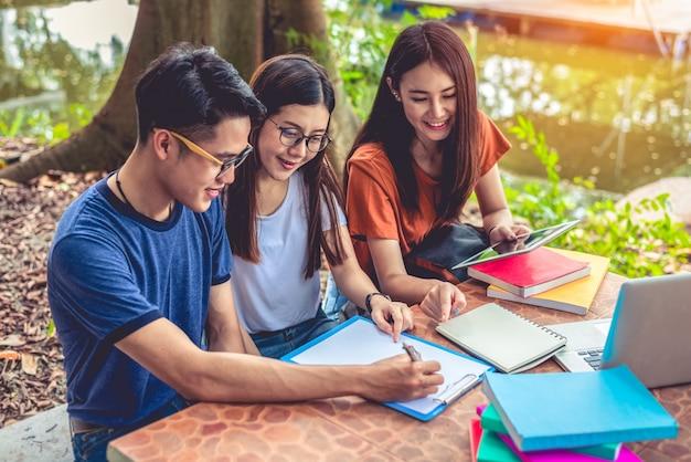 Группа азиатских студентов колледжа, чтение книг и обучения специальный класс для экзамена на стол на открытом воздухе