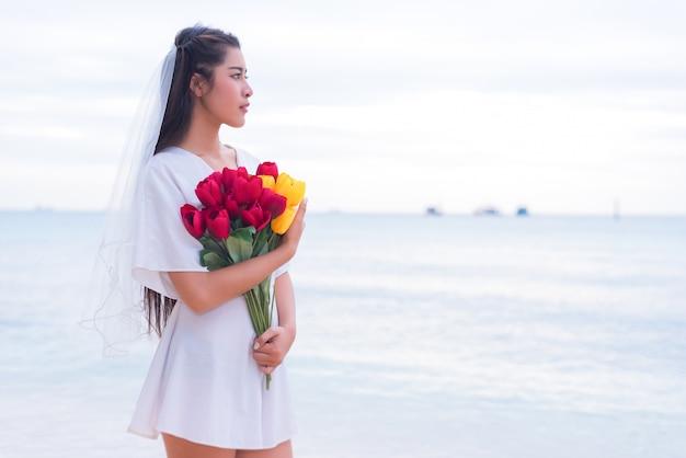 Азиатская женщина, держащая цветы и ожидающая кого-то, делает ее счастливой