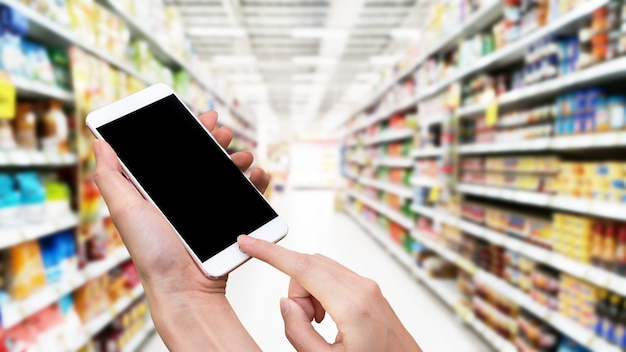 Женщина держит смартфон и кнопку касания вручную с пустым экраном для рекламы