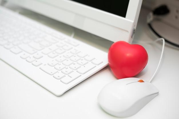 コンピュータの机のセットでオフィスで赤い心
