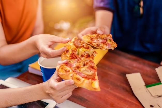 ピザを手にして祝う人々。食べ物と友情のコンセプト。ライフスタイルテーマ