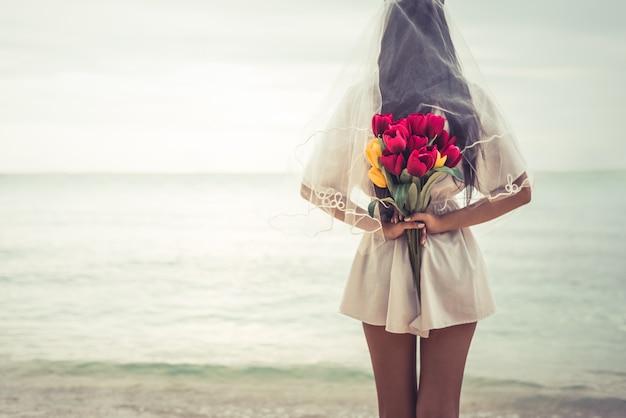 Азиатская женщина, держащая цветы сзади и ждет, когда кто-то сделает ее счастливой