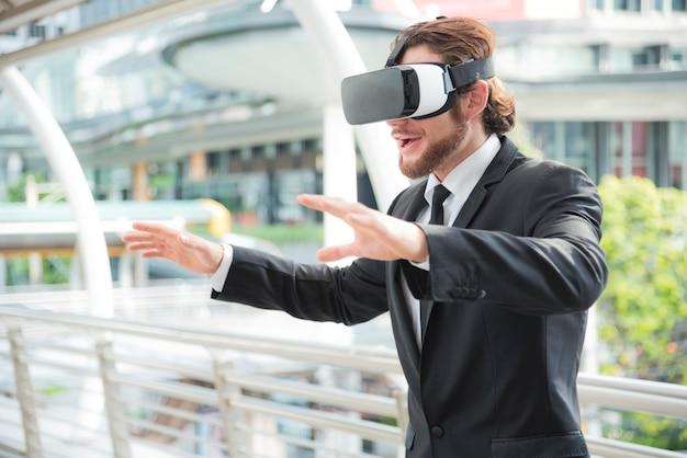 仮想現実的なゴーグルの眼鏡を着て、この活動で楽しんでいる実業家
