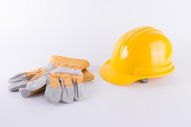 Желтый защитный шлем и защитные перчатки на белом фоне