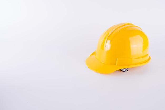 Желтый шлем безопасности на белом фоне