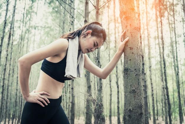 アジアの美しさの女性は疲れてジョギングから森林