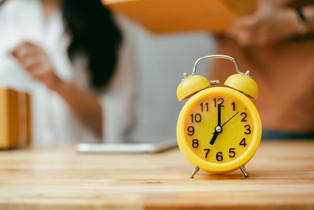 Желтый будильник на деревянном столе в офисе. женщины проверки продукта в фоновом режиме.