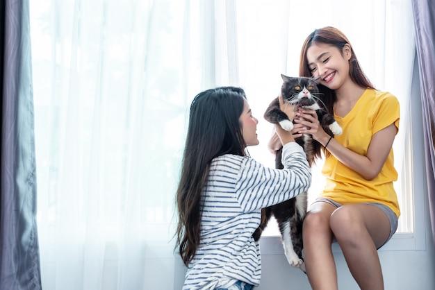 Две женщины, несущие и играющие с кошкой. концепция образа жизни и людей
