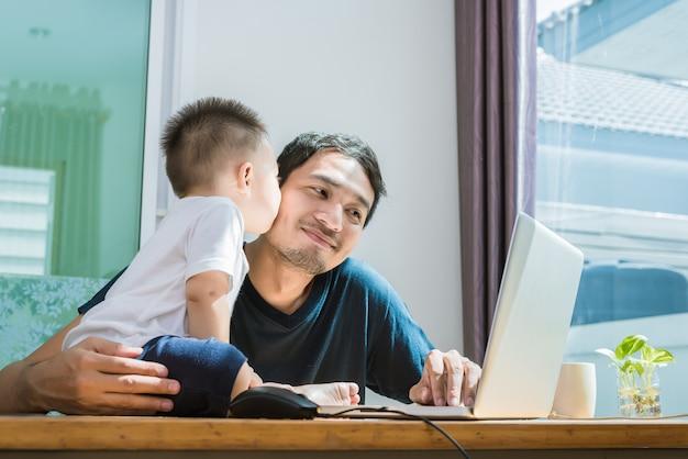 息子はインターネットを使っている間に父親にキスしています。人とライフスタイルのコンセプト。