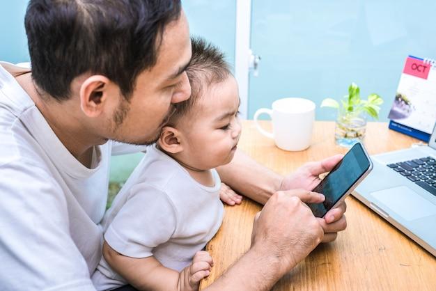 単一のお父さんと息子が一緒に楽しくラップトップを使用しています。テクノロジーとライフスタイルのコンセプト。