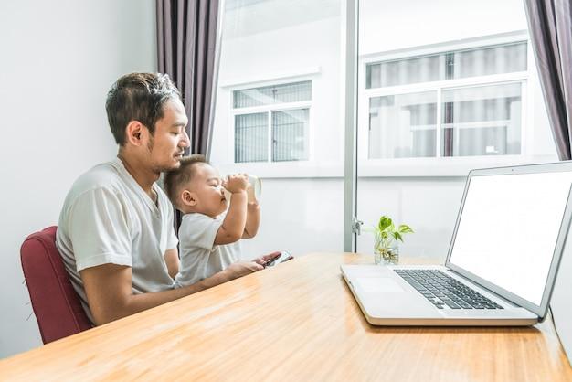スマートフォンとラップトップを家庭で一緒に使っているアジアの父と息子