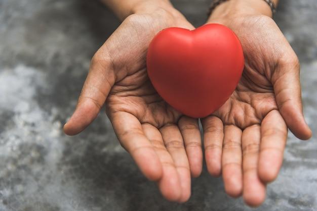 心臓ドナーとして赤い心臓を与える女性の手を閉じます。愛の概念のバレンタインデー