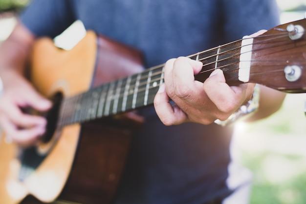 ギターを弾いているギタリストの手を閉じます。ミュージカルと楽器のコンセプト