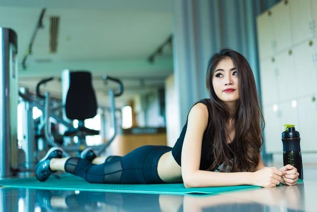 横たわって、スポーツ用具の背景とフィットネスジムのヨガマットでリラックスするスポーツの女性