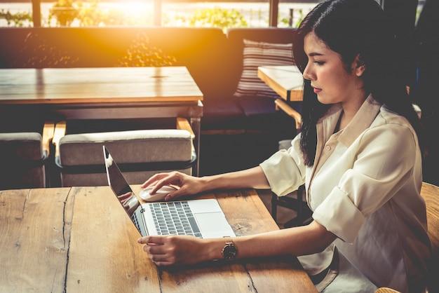 コーヒーショップでラップトップを使って作業するアジアの女性。人とライフスタイル