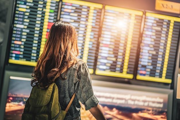 Красота женщина-турист, смотрящая на расписание полетов для проверки времени вылета