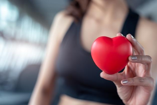 赤いマッサージボールのような心臓の形のようなフィットネスの女性の手のスポーツジムで