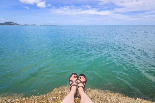 Девушка ног женщины сидит и ослабляющ на пляже.