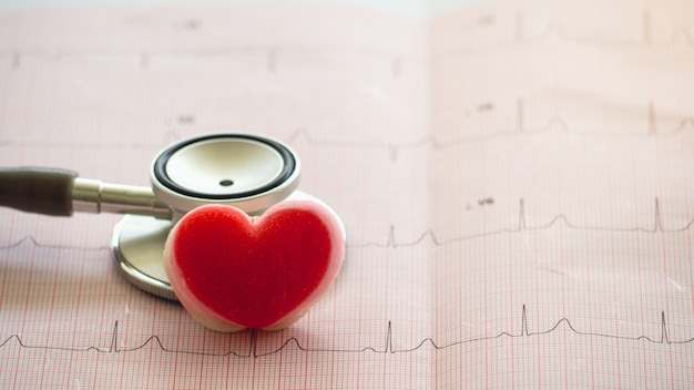 聴診器と紙の上に置かれた心臓の形は心電図を報告します。
