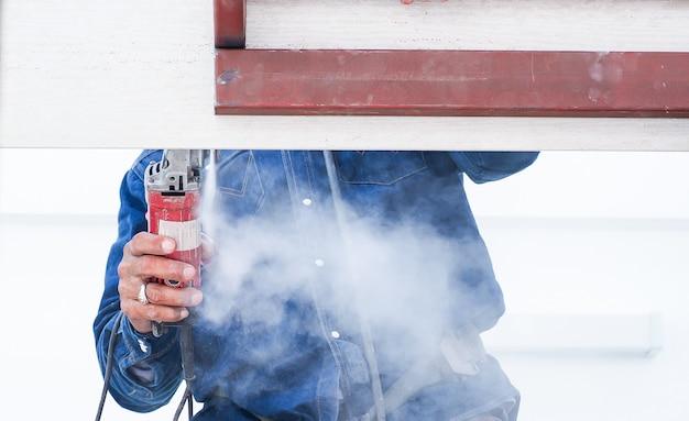 鋼鉄屋根構造に取り組んでいる建設労働者は測定および切断材料を持っています。