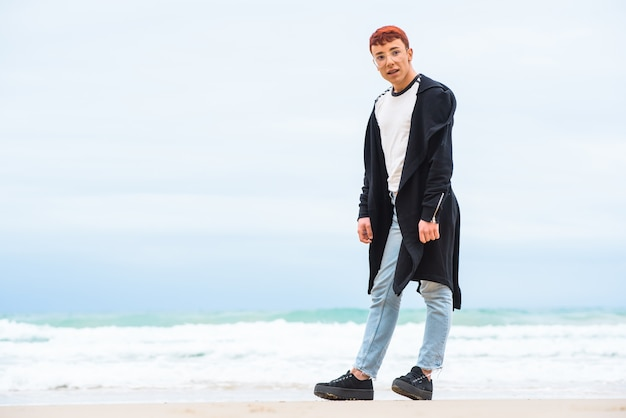 スタイリッシュな身に着けている若者がビーチでポーズします。