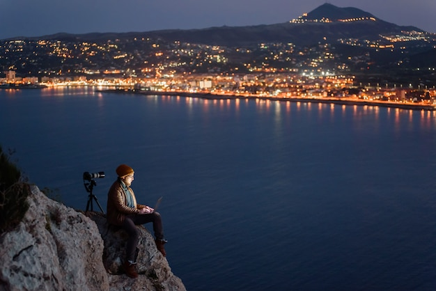 岩の上に座っていると海と山の景色を望むラップトップに取り組んでいる若い魅力的な写真家