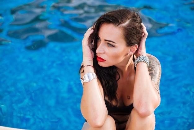 黒の水着を着てプールの近くに若いセクシーな女性