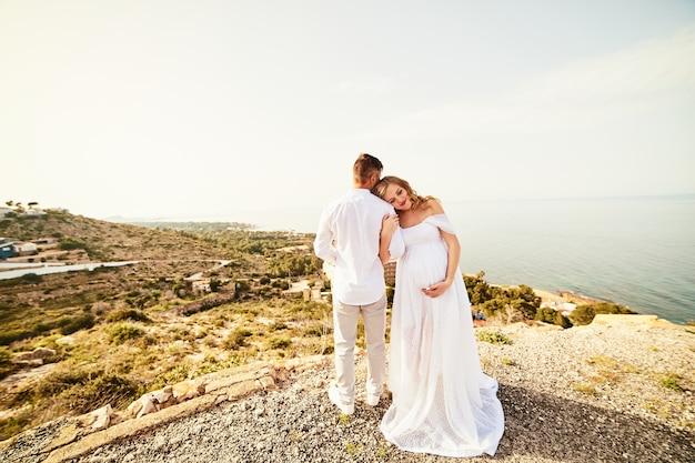 海の景色に対して夫と歩いている若い妊娠中の女性