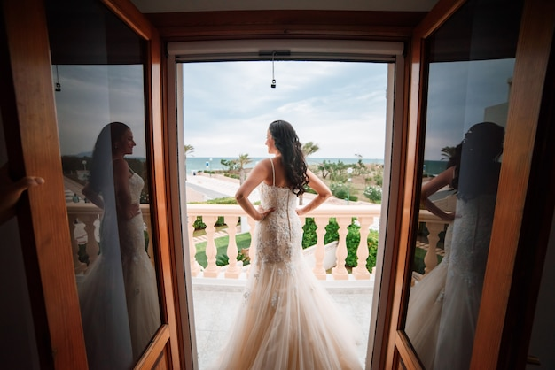 大きな窓の横に立っている美しい若い花嫁。