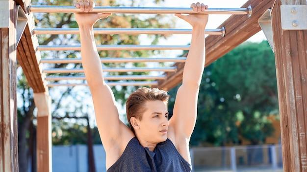 屋外の鉄棒でトレーニング男性アスリートの肖像