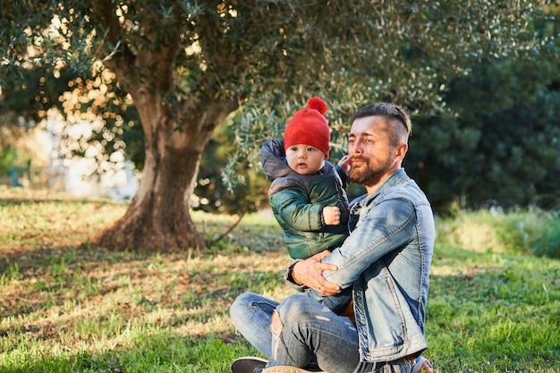 公園で幼い息子と遊んで幸せな若いひげを生やした男