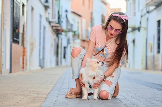 彼女の白いふわふわポメラニアンと歩く若い女の子。