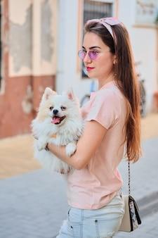 白いふわふわポメラニアンと歩いている若い女の子の肖像画。