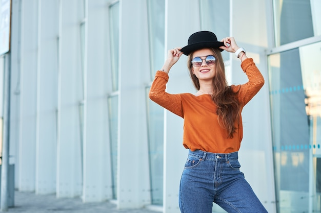 スタイリッシュな黒い帽子を着て幸せな少女