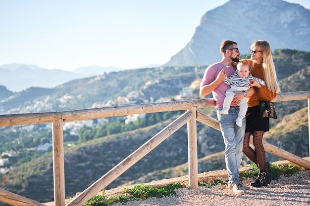 Счастливая молодая семья с маленьким милым мальчиком, наслаждаясь солнечным днем