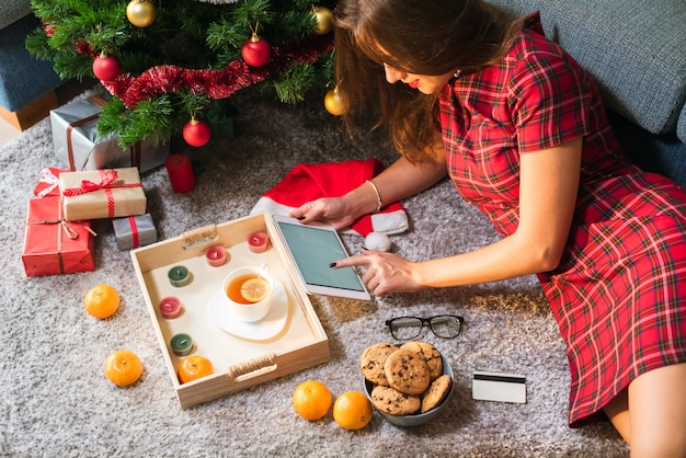 空白と床に横になっているクレジットカードを持つ女性持株タブレット。