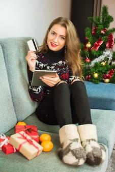 Молодая счастливая женщина, покупки в интернете с планшета и кредитной карты на рождество